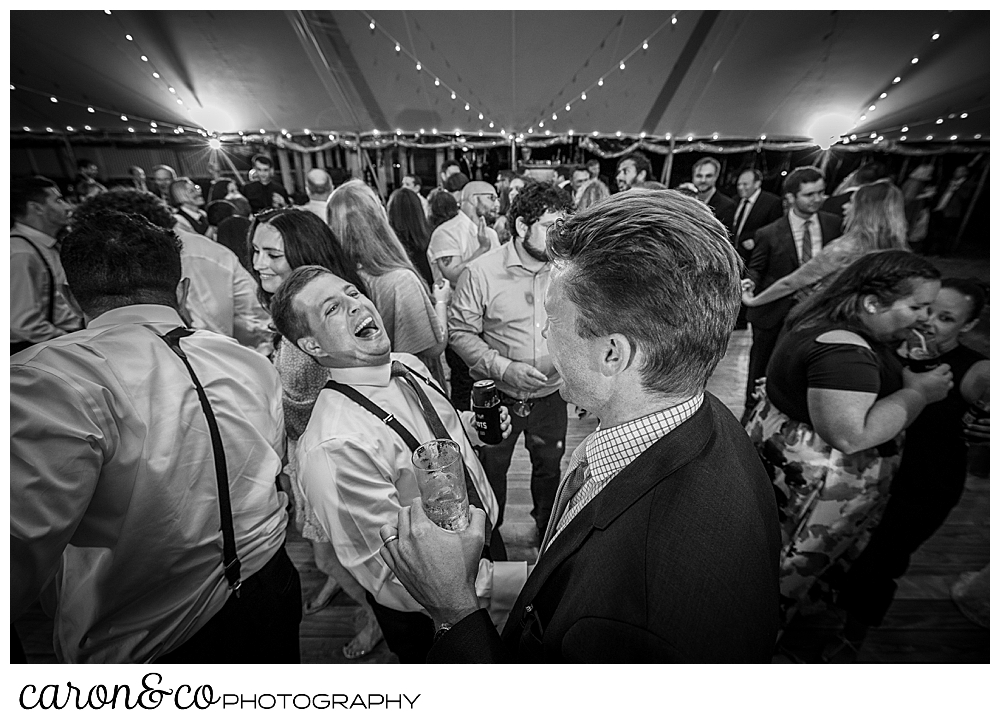 black and white photo of a groom and his friends having fun on the dance floor