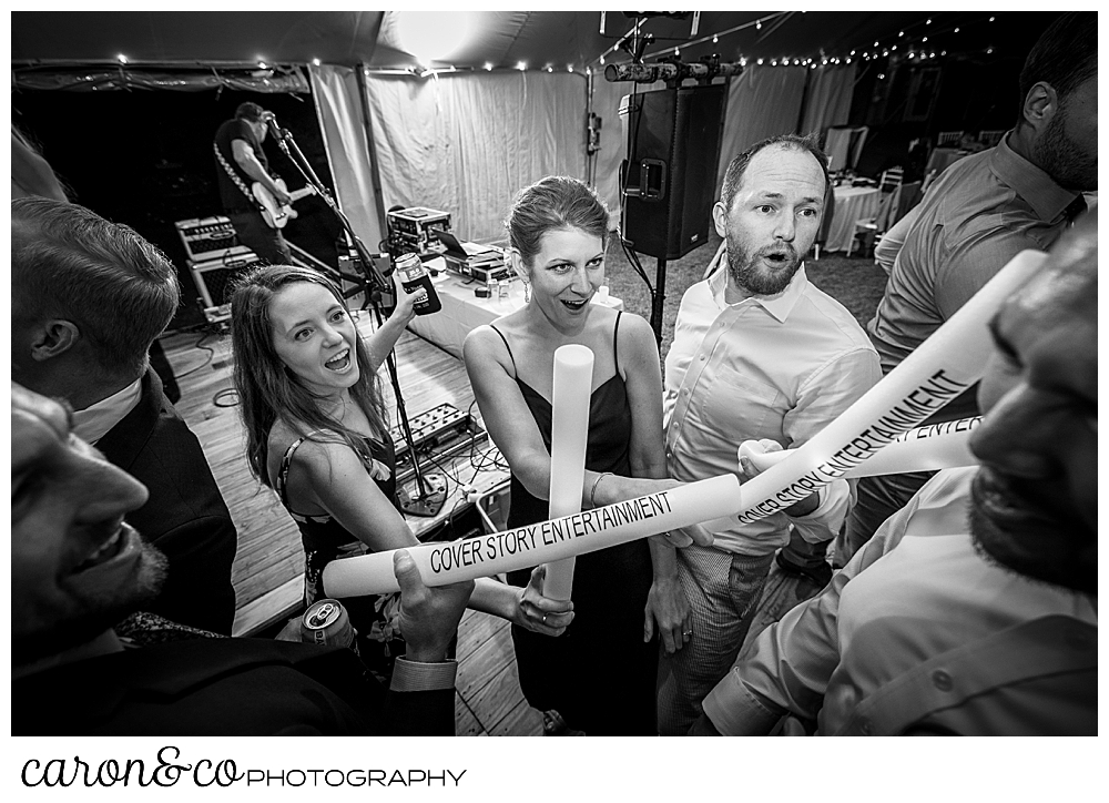 black and white photo of wedding guests with light sabers on the dance floor