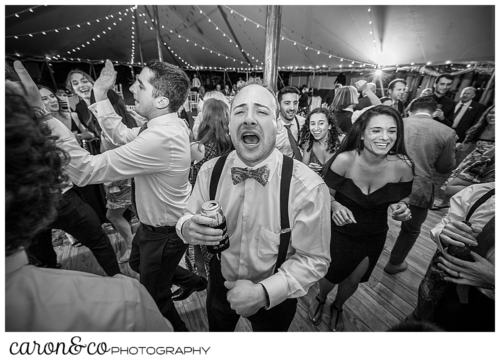 black and white photo of a wedding guests with a beer can, singing while guests around are dancing on the dance floor