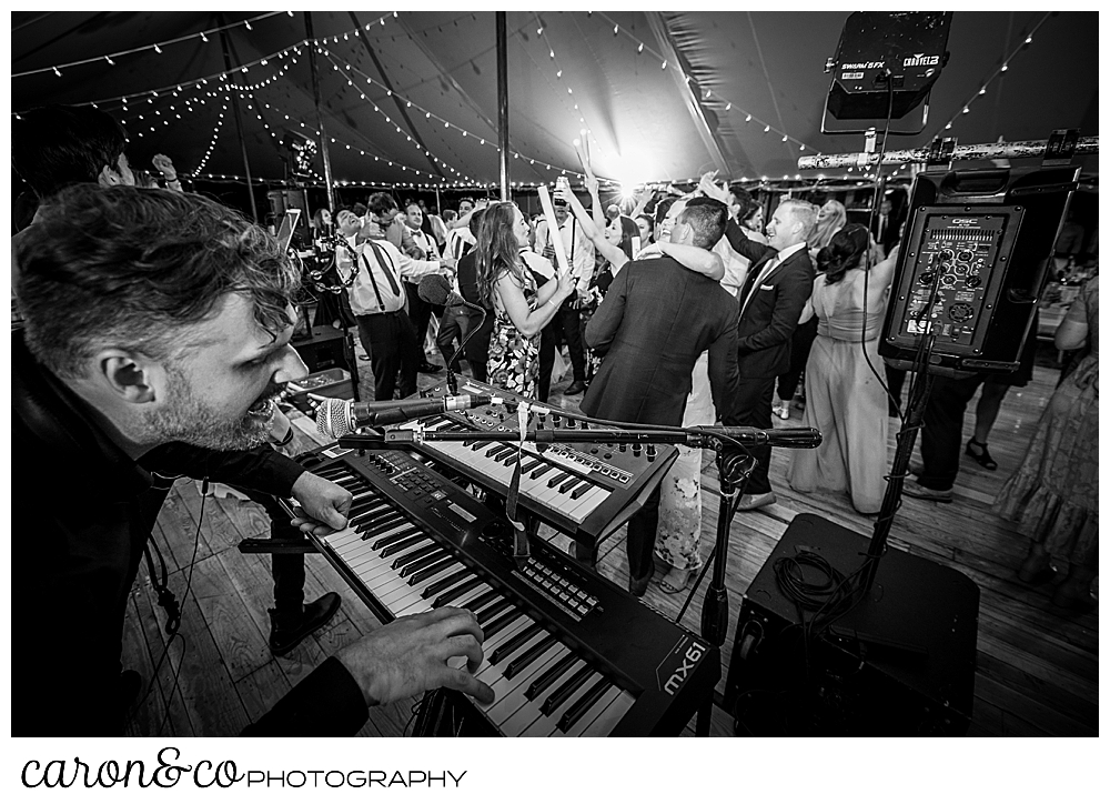 black and white photo of a keyboard player from the band Cover Story Entertainment in the foreground, and guests dancing on the dance floor in the back ground