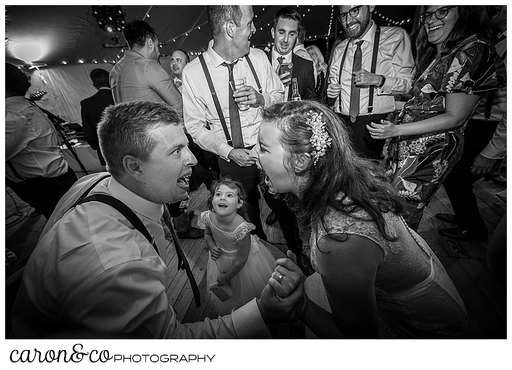 black and white photo of a bride and groom singing to each other, with a young girl watching from the dance floor of their Nonantum Resort wedding celebration