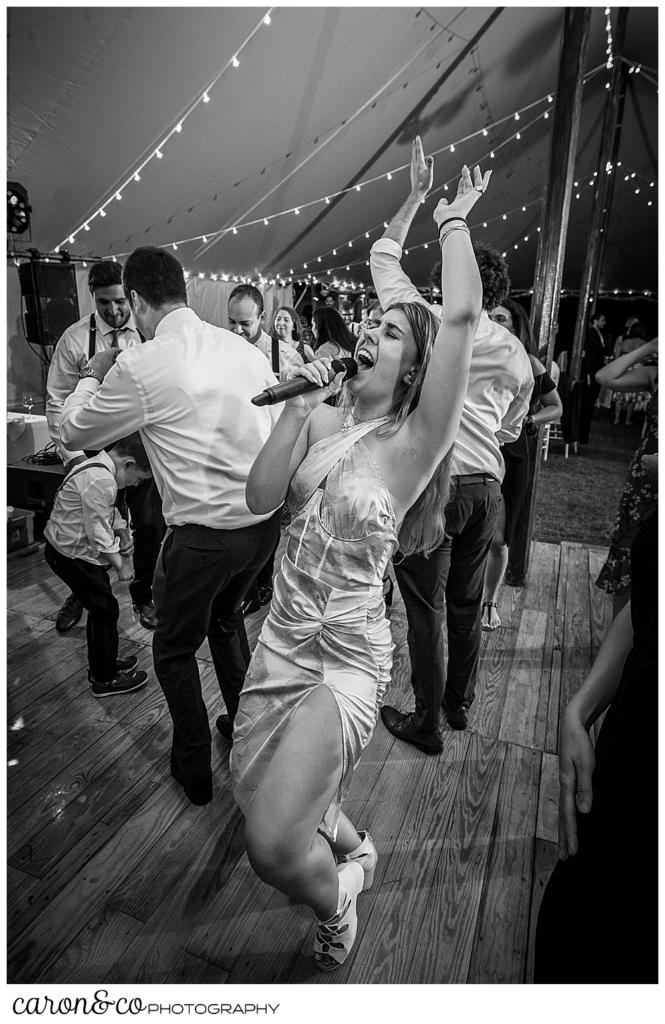 black and white photo of a female singer from the band Cover Story, in the middle of the dance floor of a Nonantum Resort wedding celebration