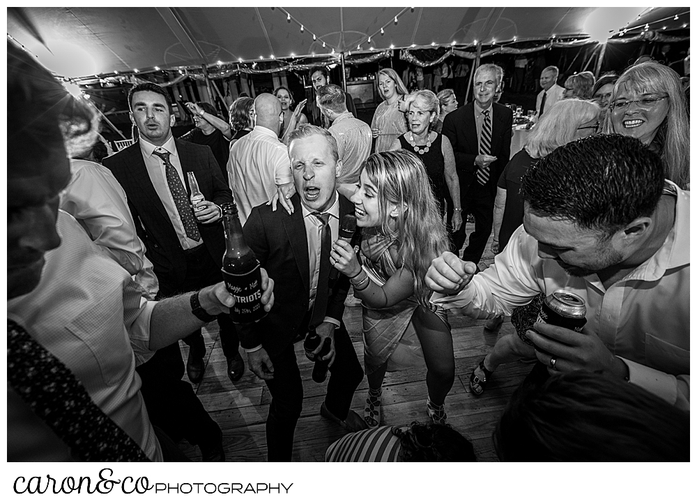 black and white photo of a singer from Cover Story Entertainment, singing with a wedding guest while guests dance at a Nonantum Resort wedding celebration