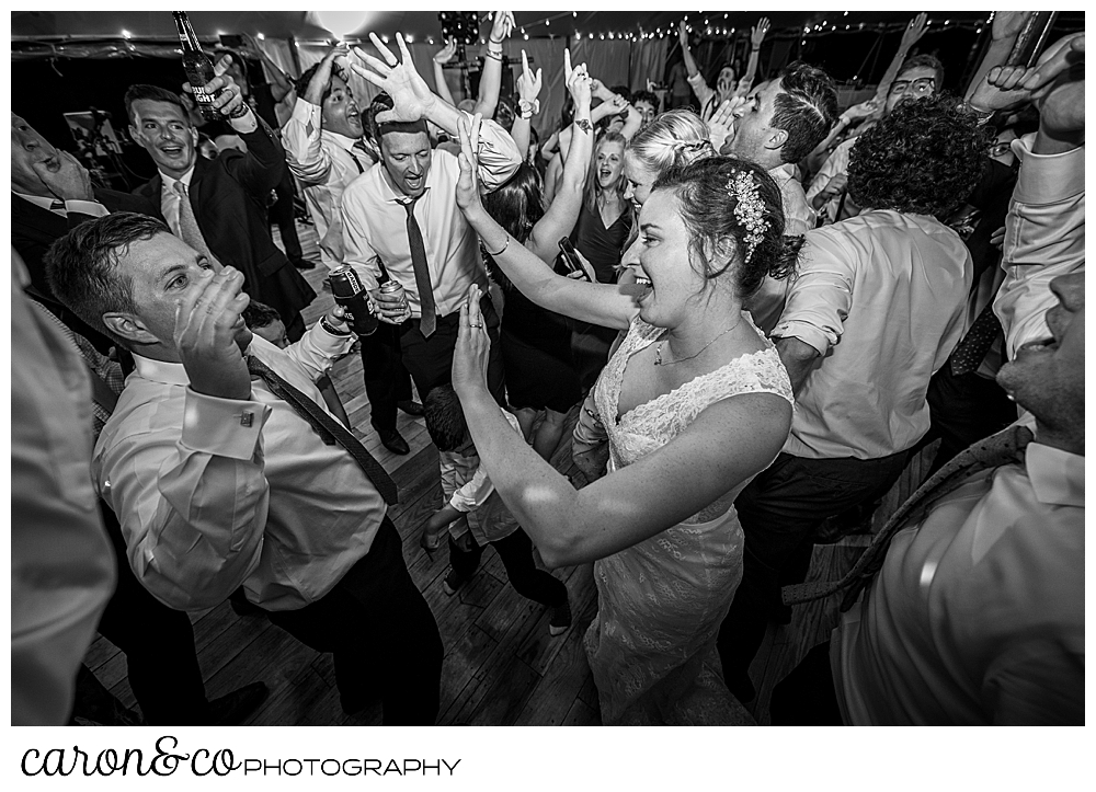 black and white photo of a bride and groom dancing with a packed dance floor, many guests have their hands up in the air
