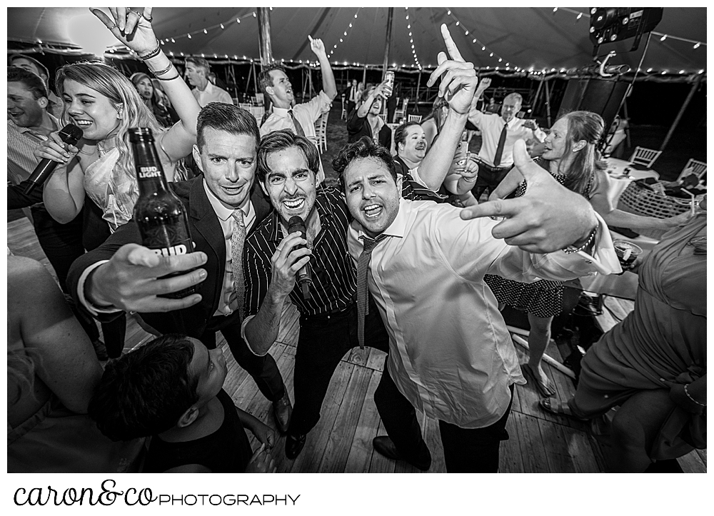 black and white photo of a singer from Cover Story Entertainment sings surrounded by two wedding guests, other guests are dancing in the background