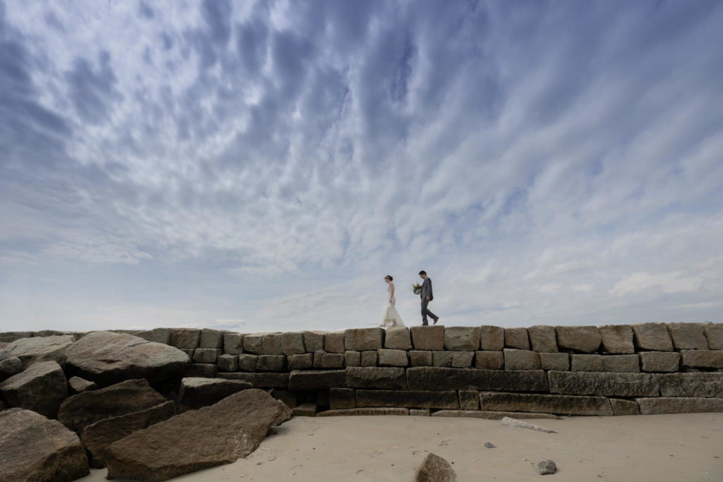 a bride and groom walk along the top of the Kennebunkport Breakwater, Kennebunkport, Maine