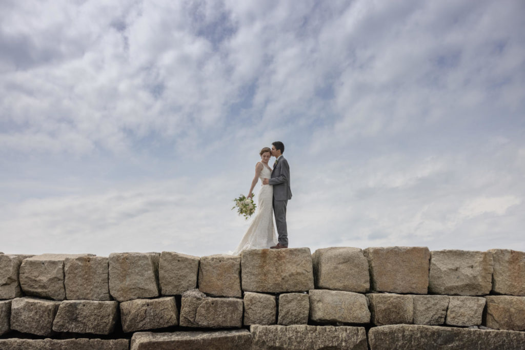 a bride and groom kiss atop the Kennebunkport Maine breakwater