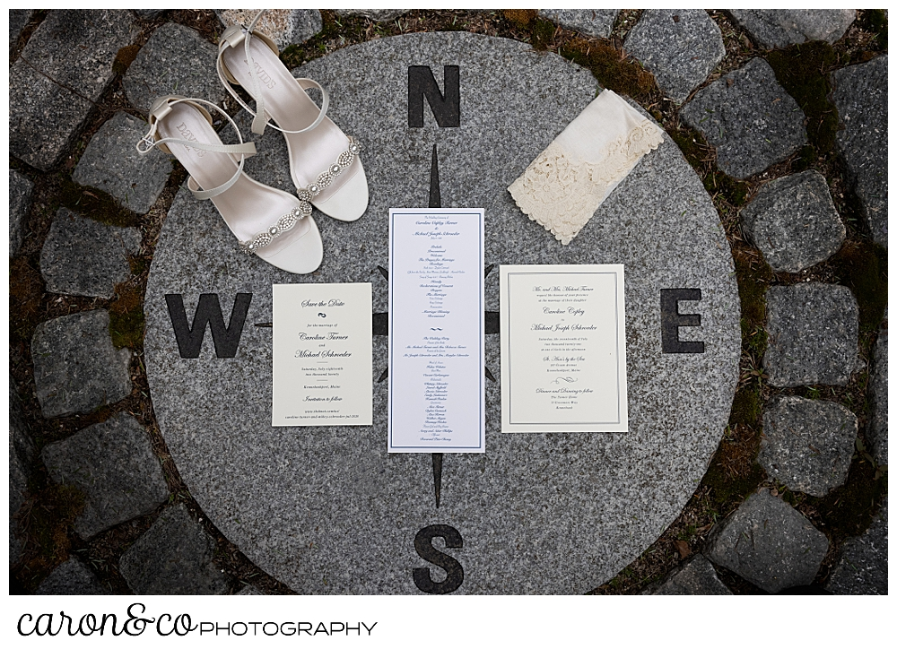bridal day details, shoes, handkerchief, and paper suite arranged in a compass rose inlay of stone in a garden