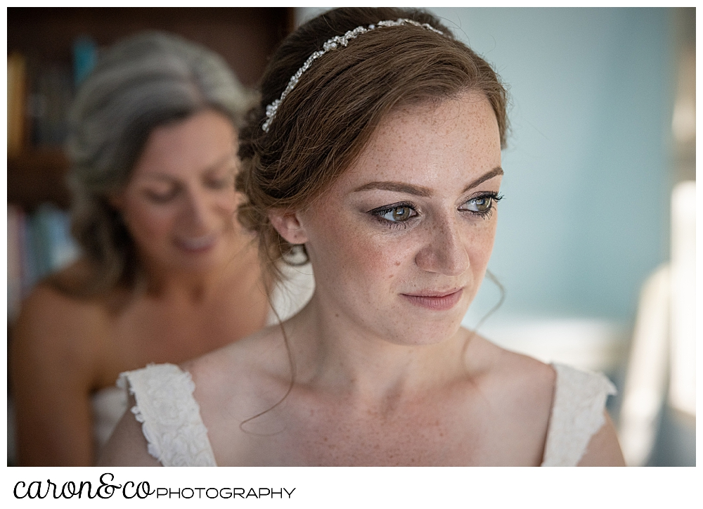 a bride gets ready, with her mother standing behind, helping with her dress