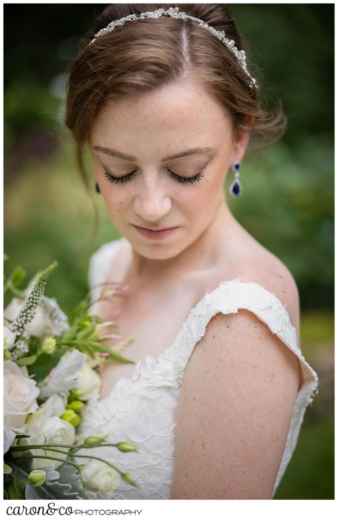 a beautiful bride with her eyes closed, holding a bouquet