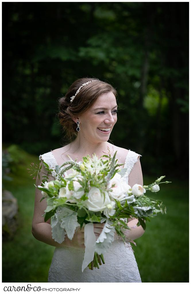 a beautiful portrait of a bride, holding a bouquet of white, pink, and green, and smiling at someone off camera