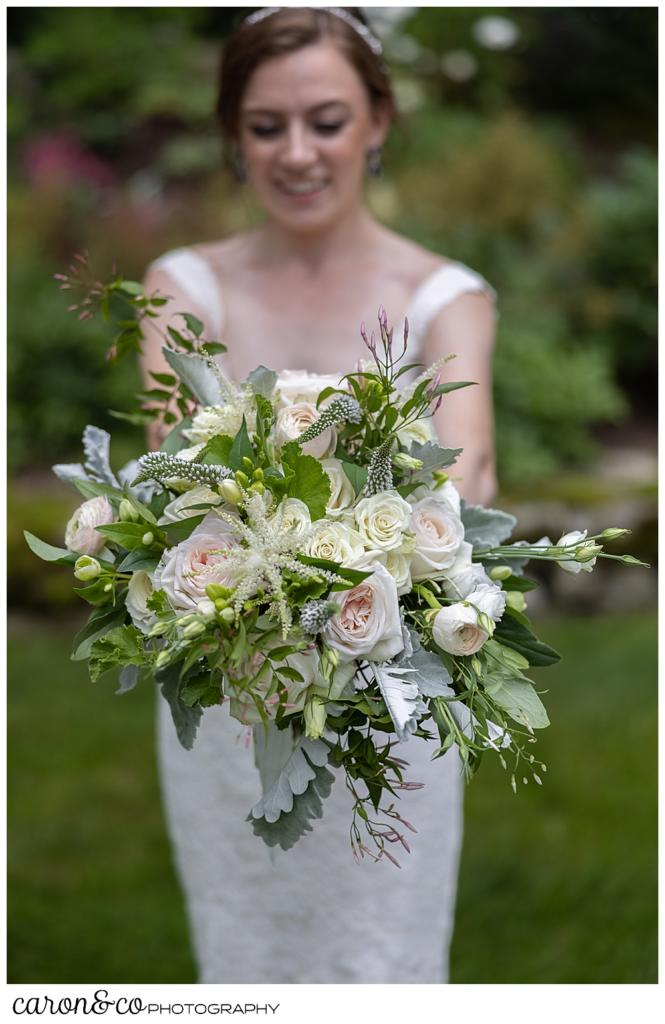 bride holding a beautiful bridal bouquet by Fleurant Designs, the flowers are pastel pink, white, cream, and green