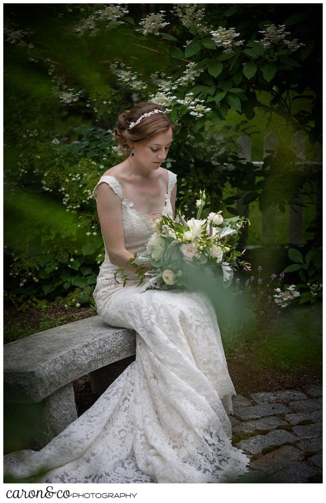 a bride sits on a granite bench in a small garden