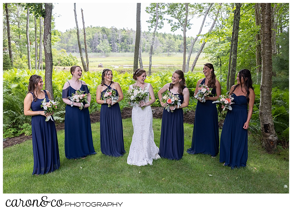 a bride wearing a white dress, and her six bridesmaids wearing blue, stand together in a woodland garden