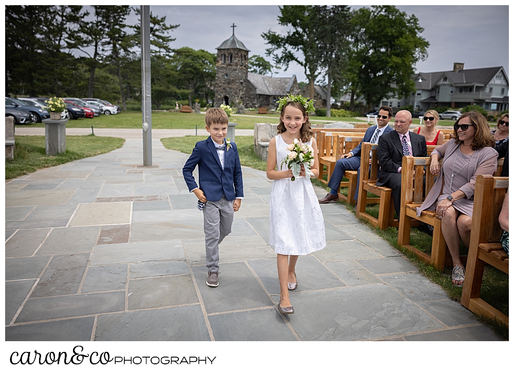 a flower girl and a ring bearer walk down the aisle of the outdoor ceremony site at St. Ann's by-th-sea Episcopal Church, Kennebunkport, Maine