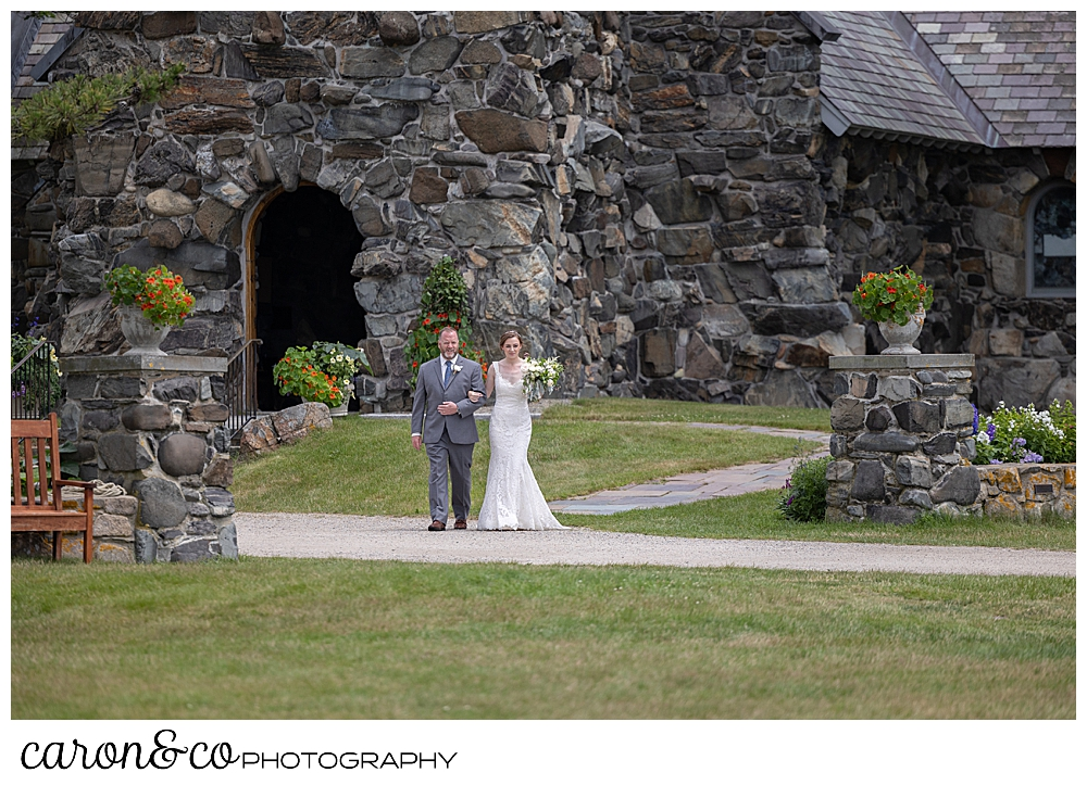 A bride and her father walk from St. Ann's by-the-sea Episcopal Church in Kennebunkport, Maine, toward the outdoor ceremony site