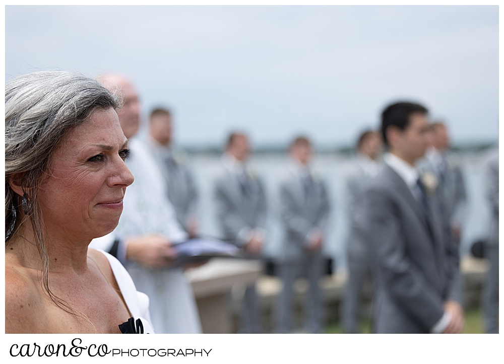 mother of the bride, in the foreground, and groom in the background, watches the bride and her dad walk down the aisle at St. Ann's by-the-sea Episcopal Church, Kennebunkport, Maine