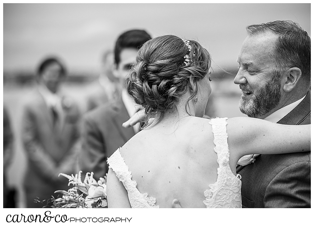 A black and white photo of a bride and her father as they part at the end of the aisle at a St. Ann's by-the-sea Episcopal Church outdoor ceremony