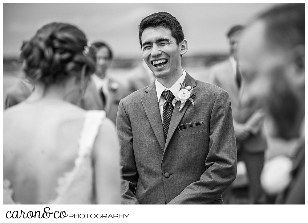 black and white photo of a groom laughing during the wedding ceremony