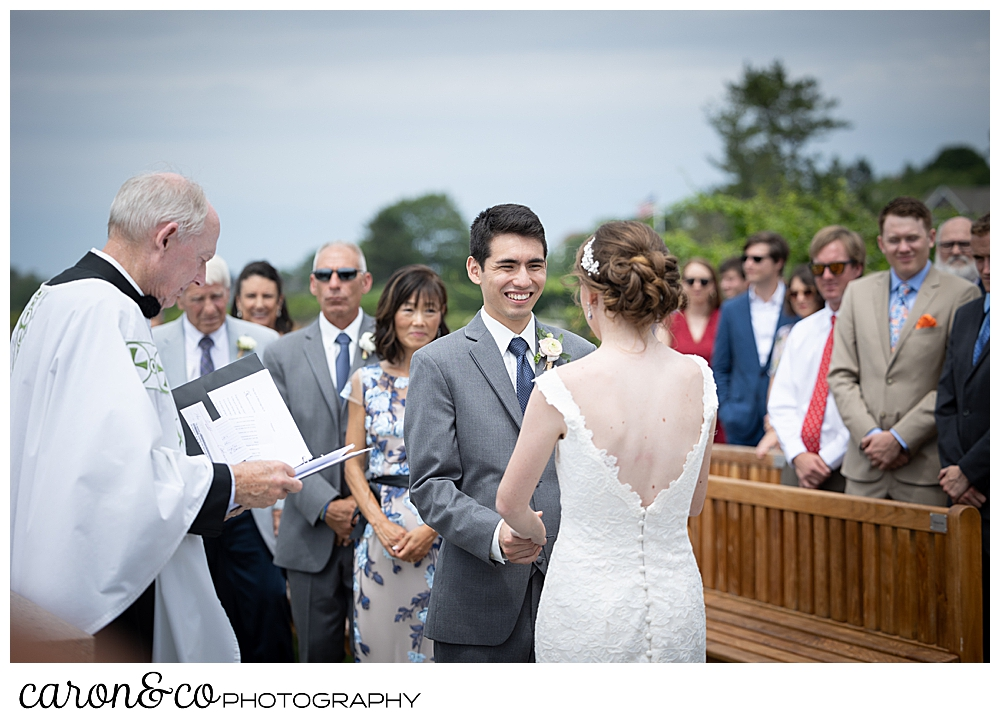 a groom smiles at his bride during a St. Ann's by-the-sea Episcopal Church, Kennebunkport, Maine