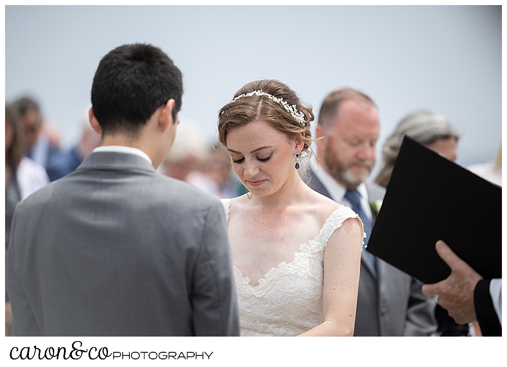 a bride bows her head during an outdoor wedding ceremony
