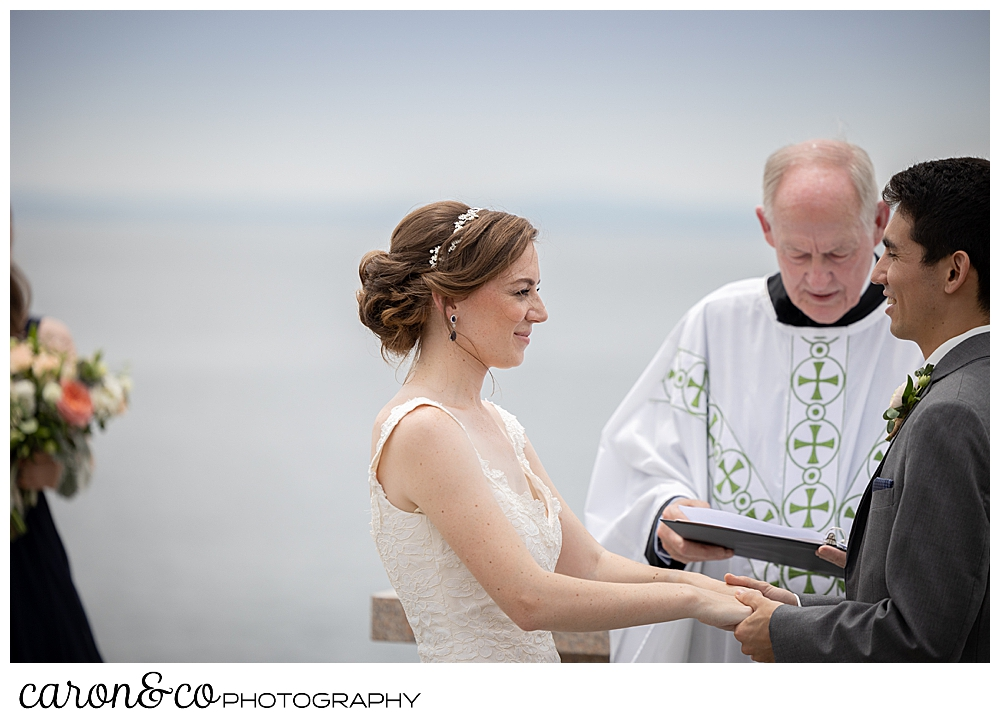 a bride looks at her groom during an outdoor wedding ceremony