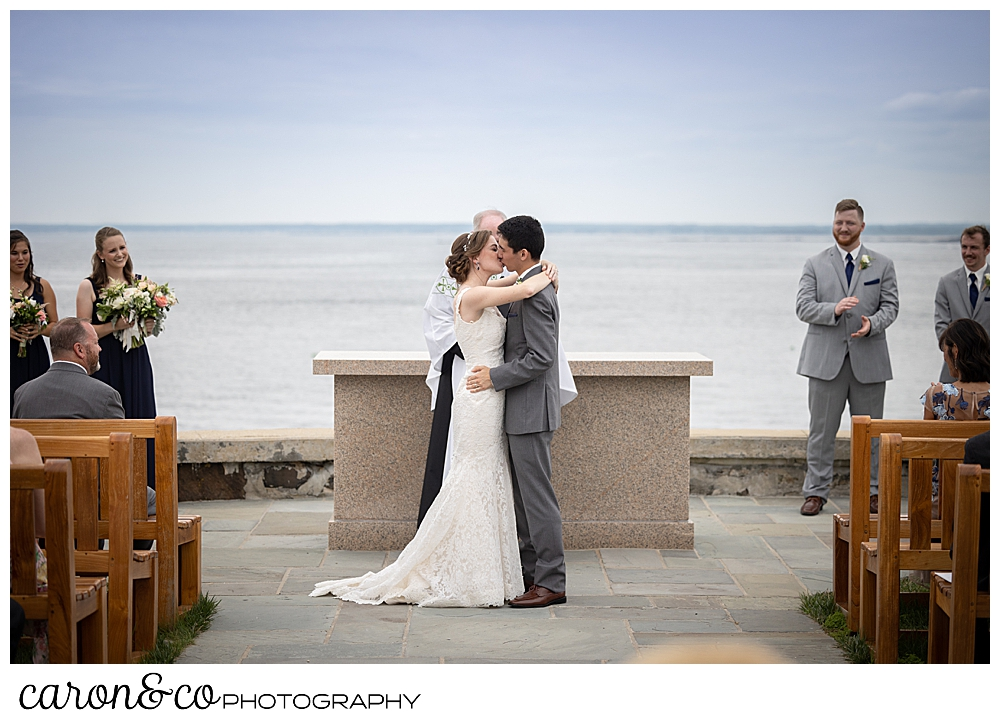 a bride and groom's first kiss at St. Ann's by-the-sea Episcopal Church outdoor ceremony site, Kennebunkport, Maine