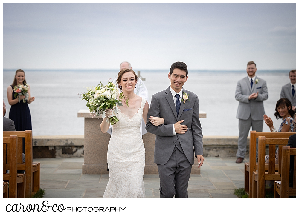 a bride and groom during their recessional at a St. Ann's by-the-sea Episcopal Church outdoor ceremony, Kennebunkport, Maine