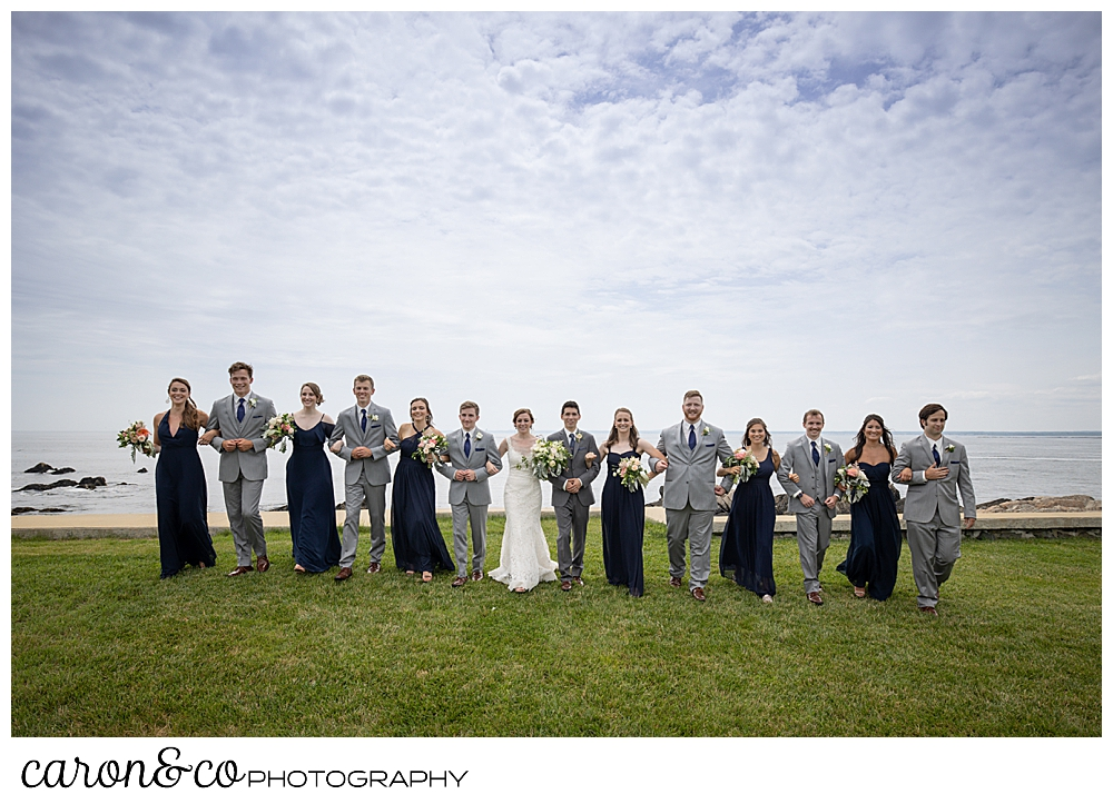 a bridal party walks arm-in-arm at St. Ann's by-the-sea Episcopal Church, Kennebunkport, Maine