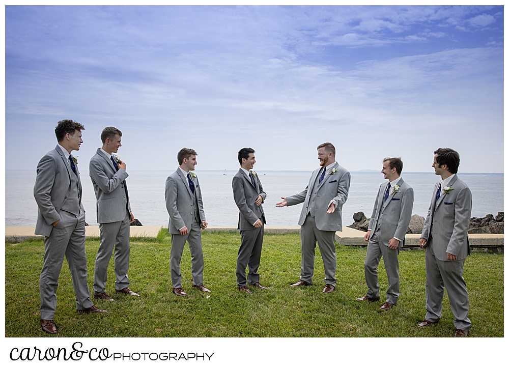 a groom and six groomsmen stand together, laughing