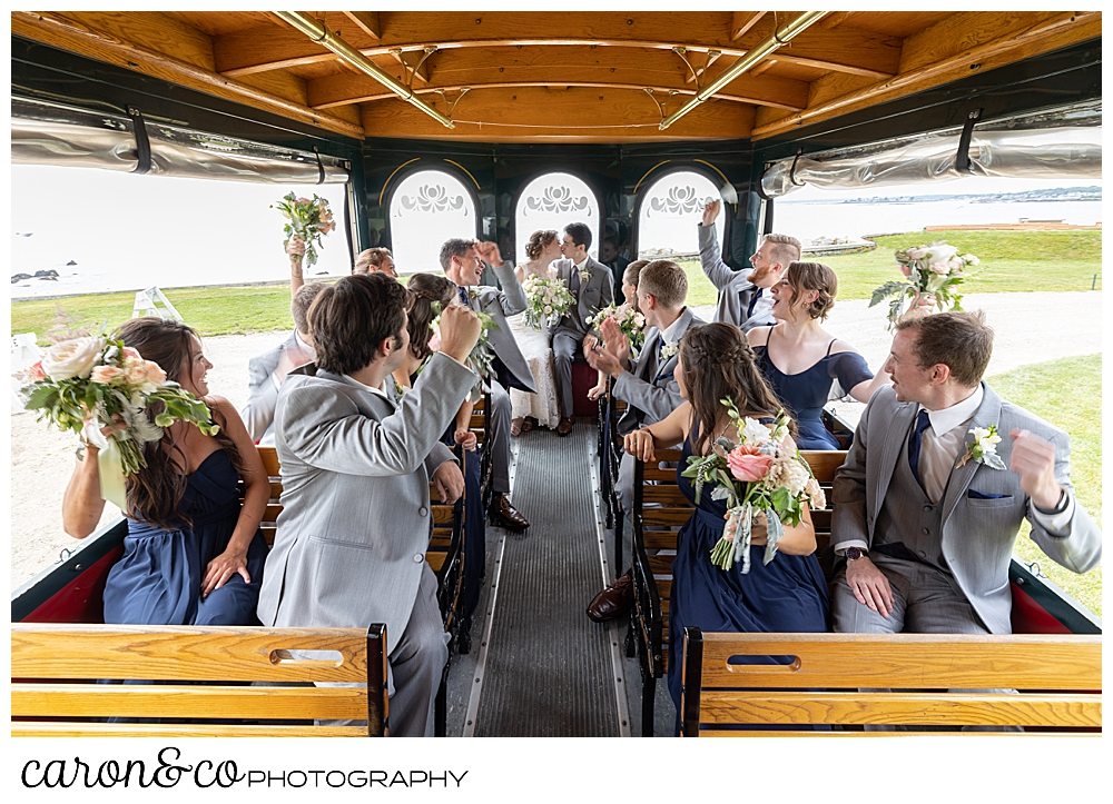 a bride and groom kiss on a trolley, while their bridal party cheers