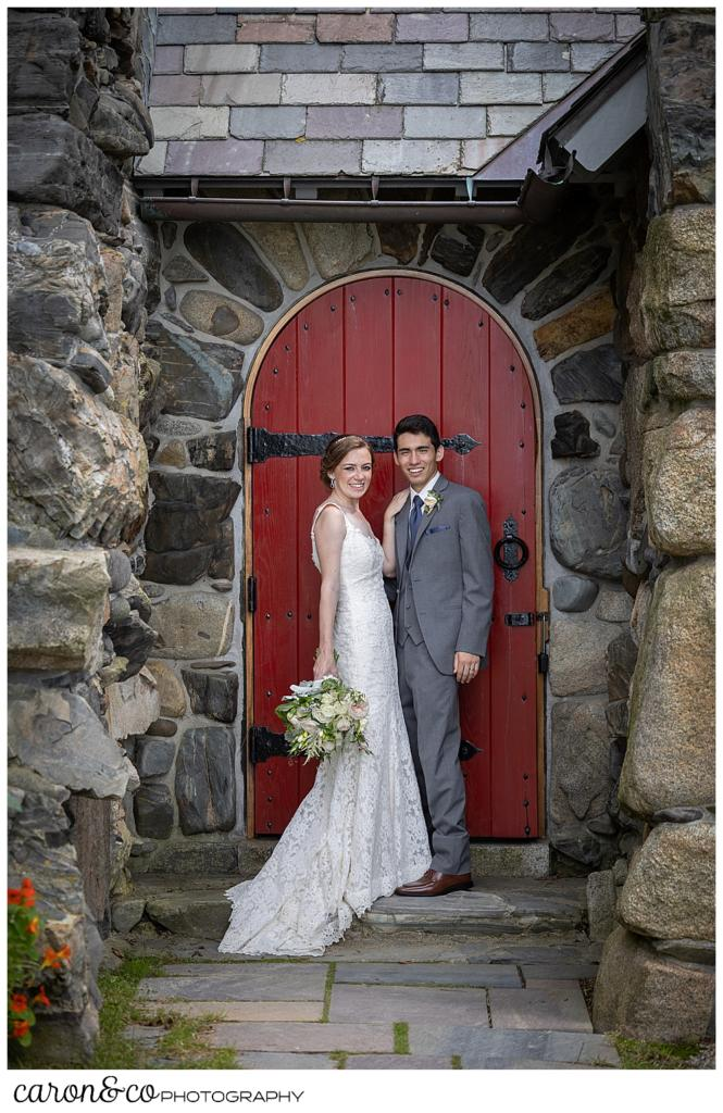 a bride and groom stand in front of a red door at St. Ann's by-the-sea Episcopal Church, Kennebunkport, Maine