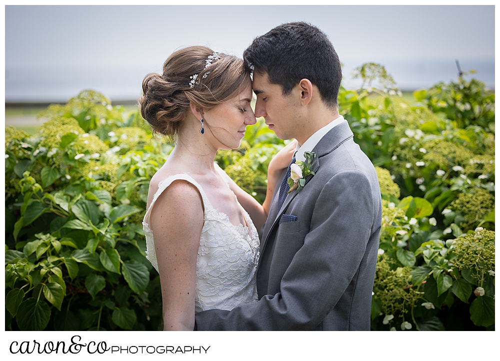 a bride and groom stand in a garden, forehead to forehead