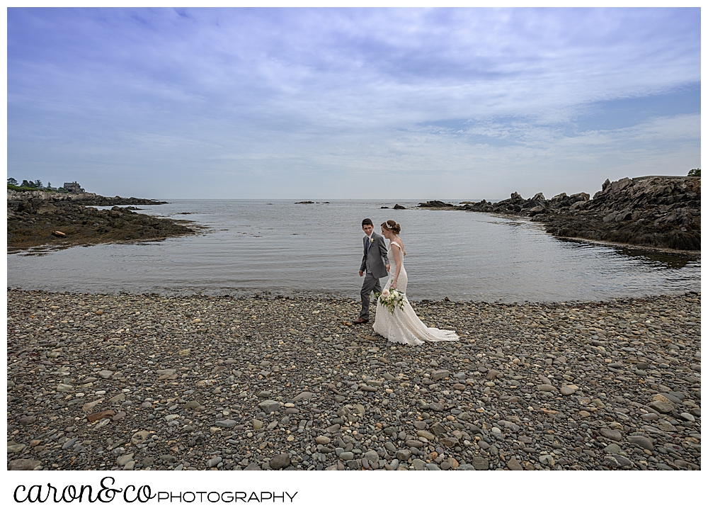 a bride and groom walk on a Kennebunkport Beach, during their Kennebunk Maine wedding