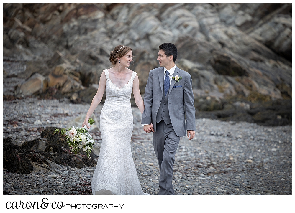 a bride and groom walk hand in hand on a rocky beach in Kennebunkport, Maine