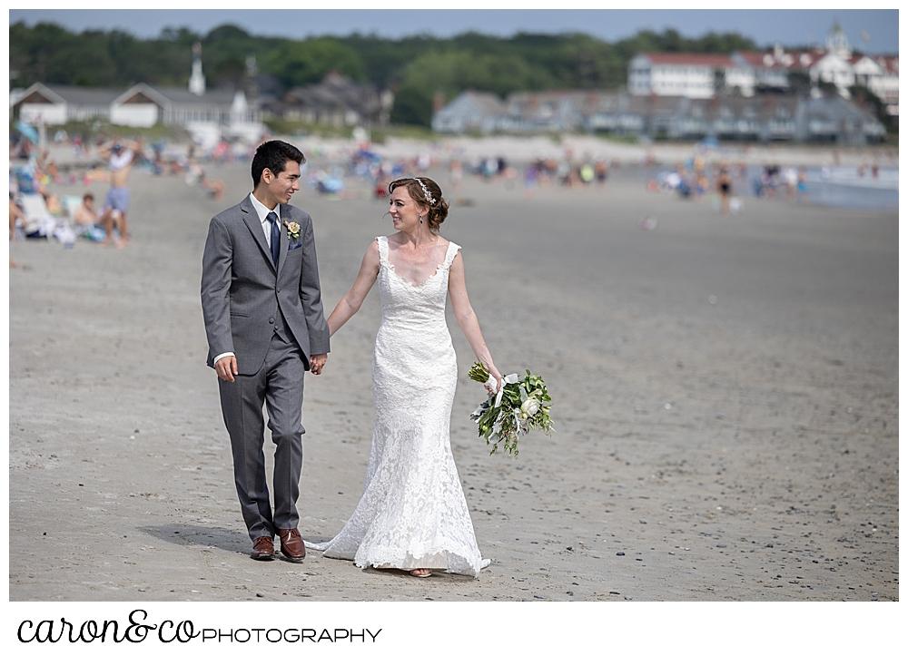 a bride and groom walk on Gooch's Beach in Kennebunk, during their Kennebunk Maine wedding