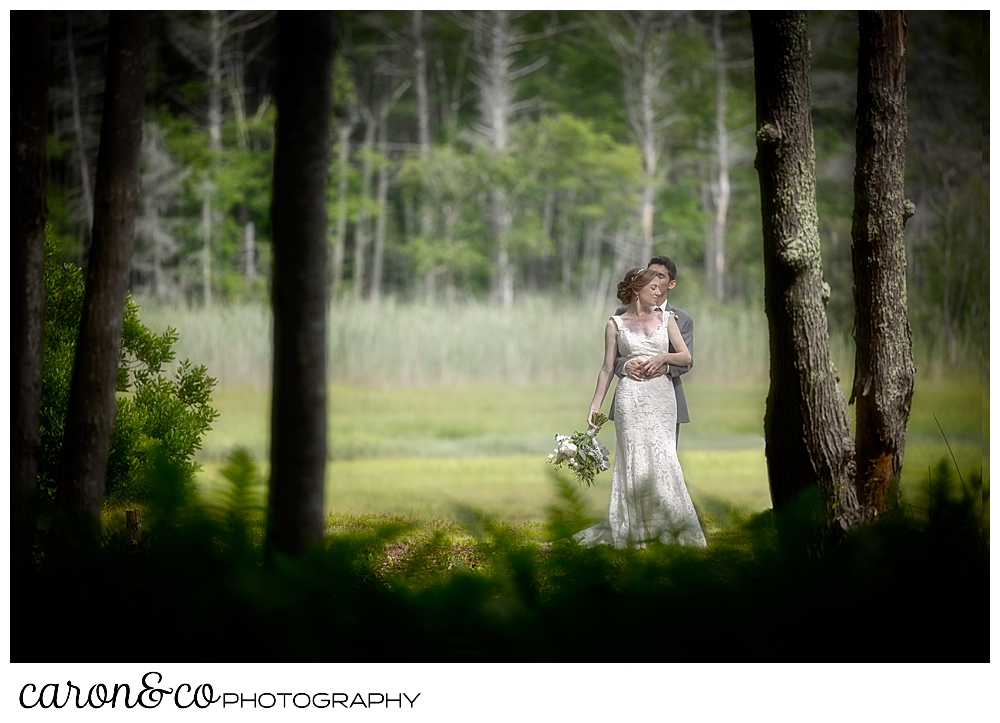 a groom hugs his bride in a a wooded garden, during their Kennebunk Maine wedding reception