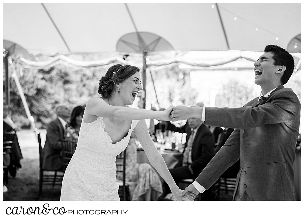 black and white photo of a bride and groom dancing and laughing during their first dance at a Kennebunk Maine wedding reception