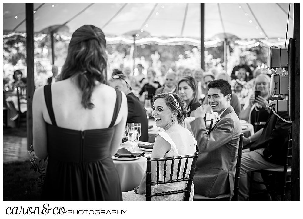 a bridesmaid with her back to the camera, proposes a toast to the bride and groom, who are looking on during their Kennebunk Maine wedding reception