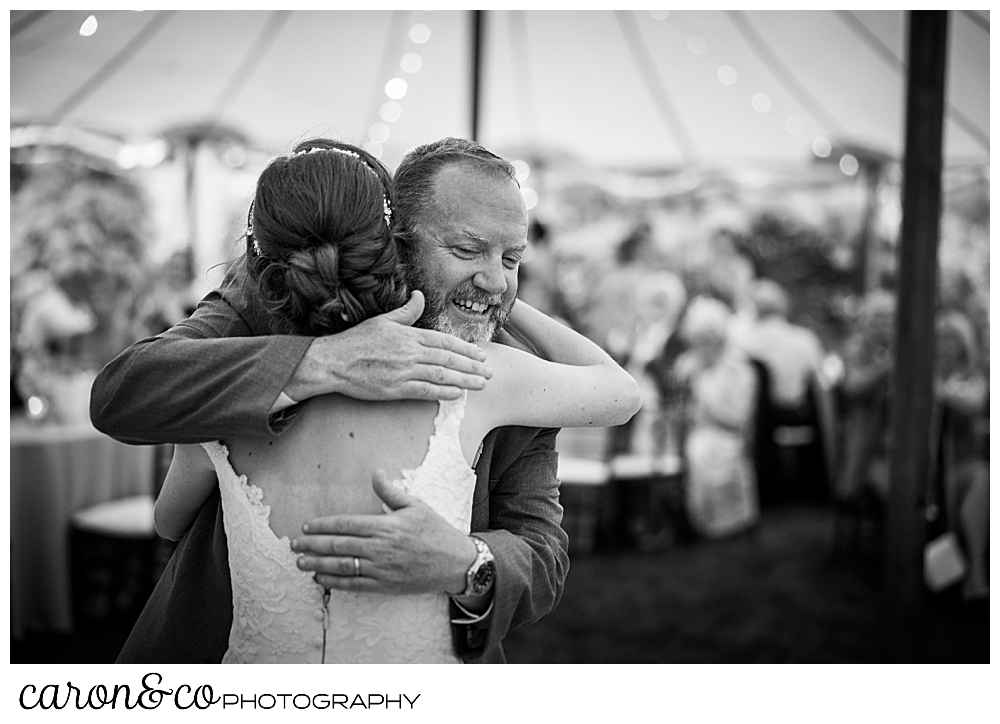 black and white photo of a bride hugging her father after the father daughter dance, at a Kennebunk Maine wedding reception