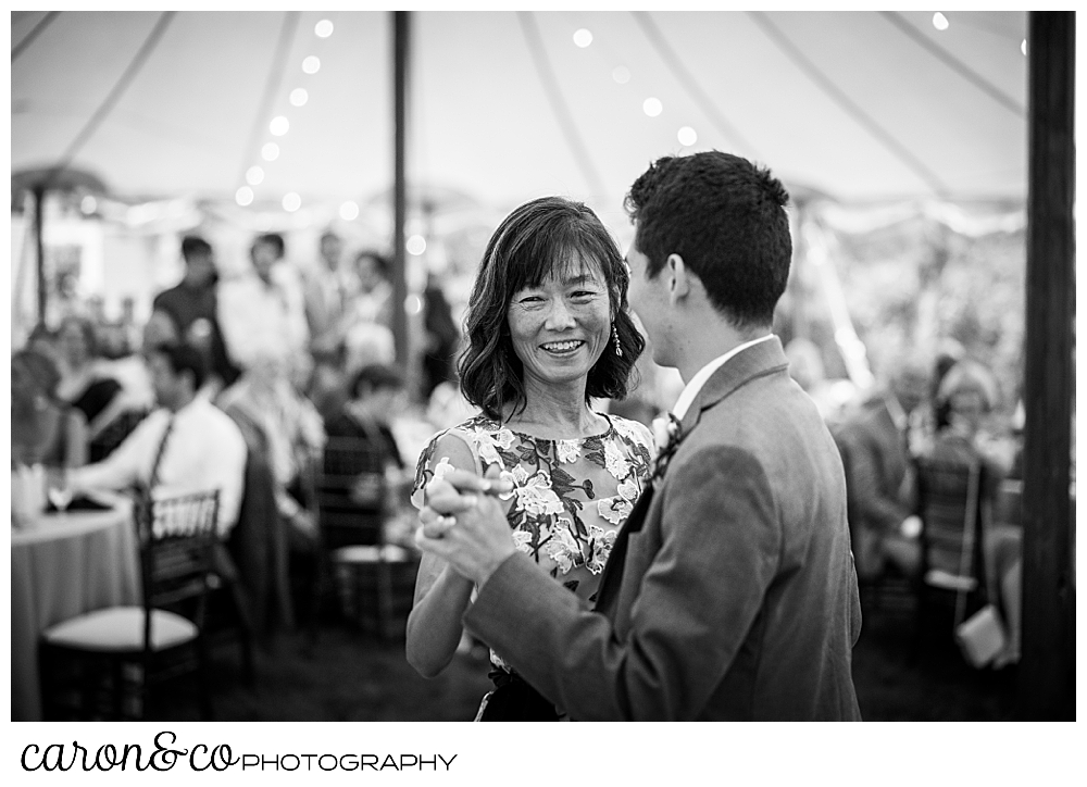 black and white photo of the mother of the groom smiling during the mother son dance at a Kennebunk Maine wedding reception