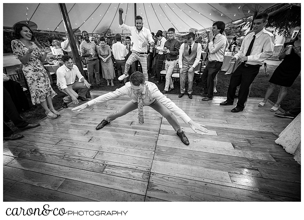 black and white photo of a man dancing, his arms and legs spread wide, during a tented Kennebunk Maine wedding reception