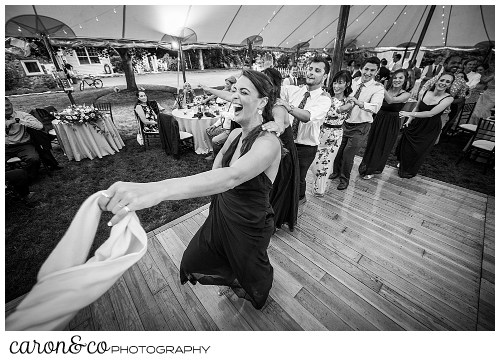 black and white photo of a woman holding onto a scarf, she is leading a conga line dance during a tented Kennebunk Maine wedding reception