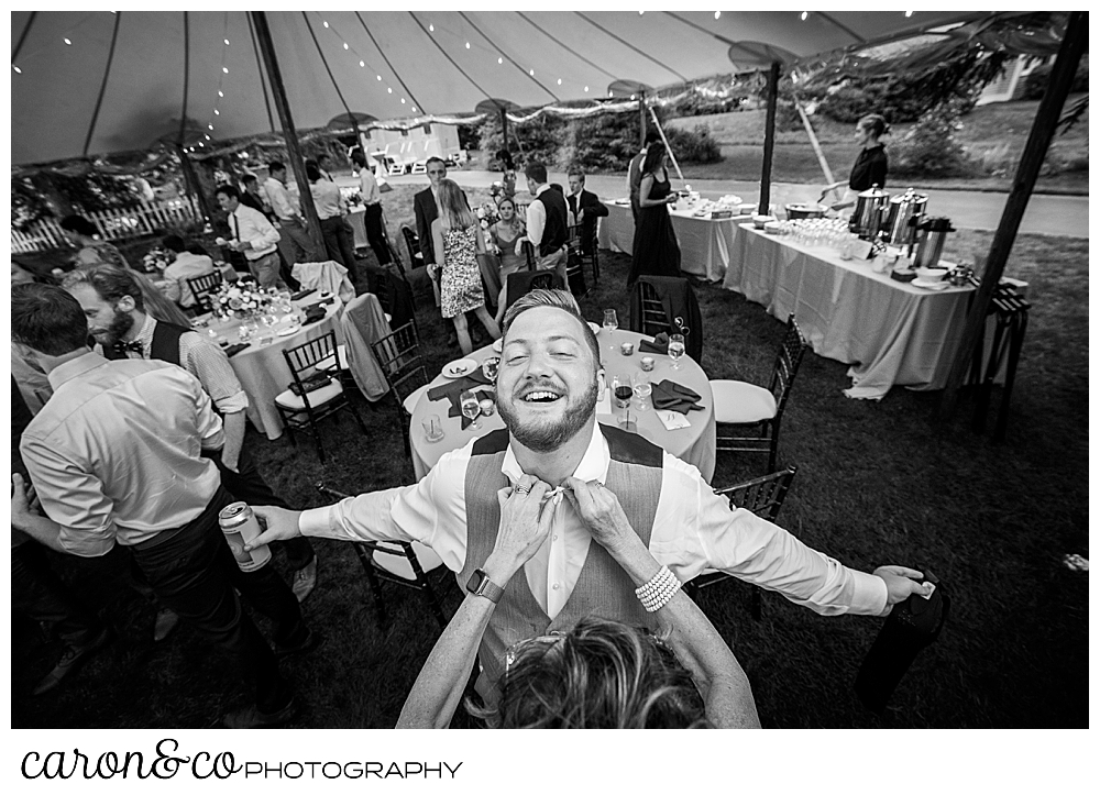black and white photo of a woman removing a tie from a man who is laughing and holding his arms out during a coastal Kennebunk Maine wedding reception