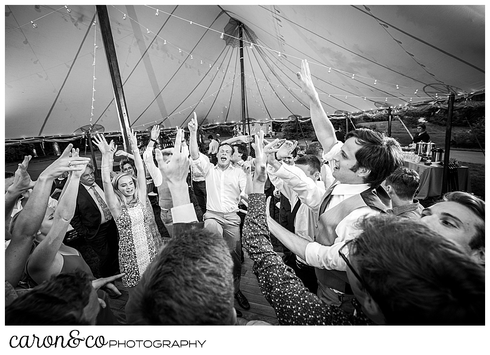 black and white photo of guests dancing with their arms raised, during a tented Kennebunk Maine wedding