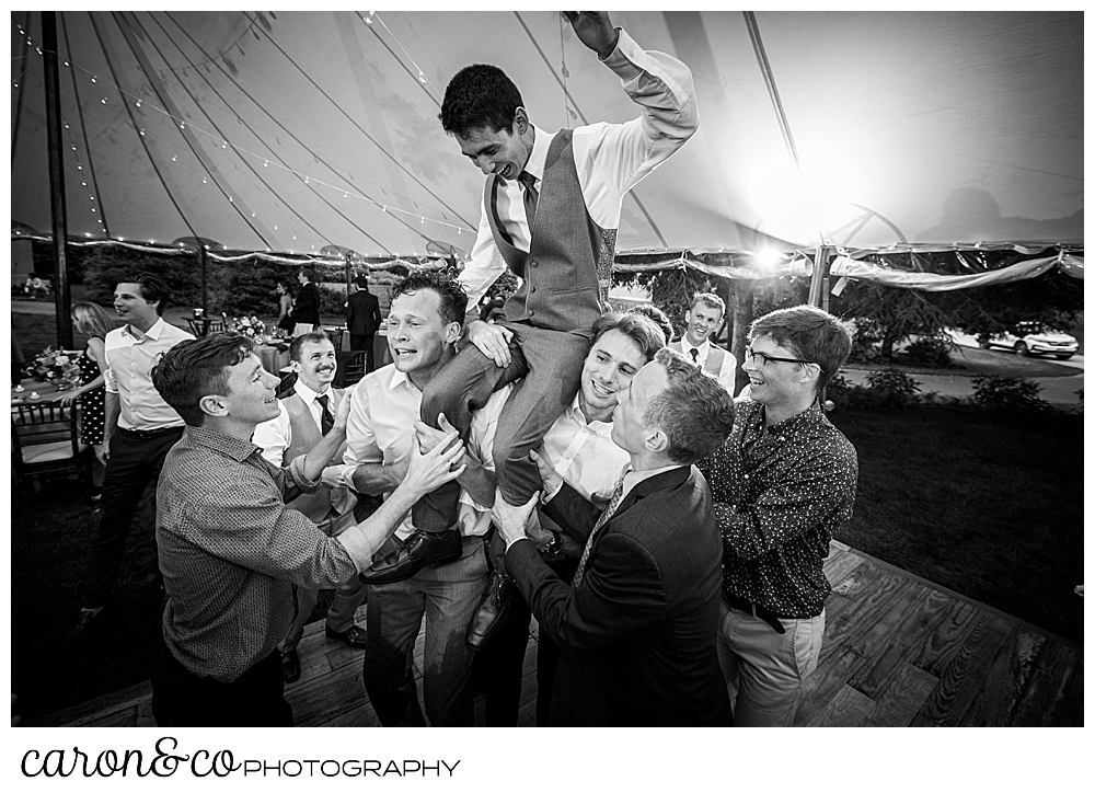 black and white photo of a groom being raised up on his friends shoulders, during a coastal Maine tented wedding