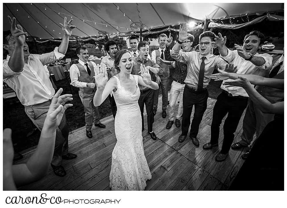 black and white photo of a bride standing on the dance floor, surrounded by guests who are singing during a Maine coast tented wedding