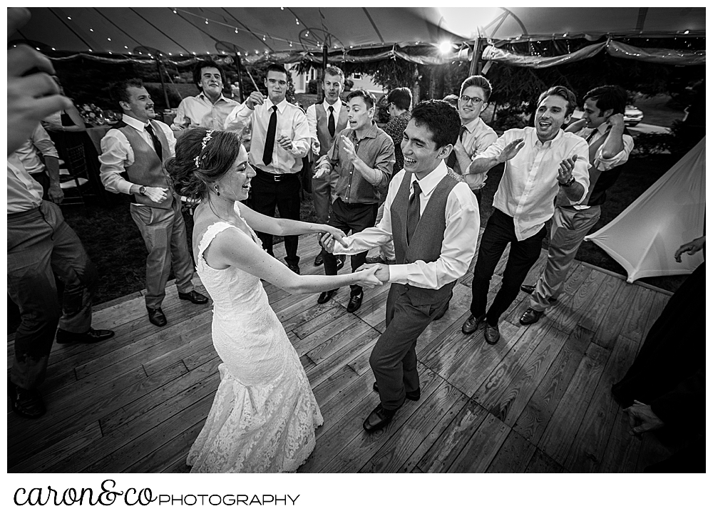 black and white photo of a bride and groom dancing, surrounded by friends at a coastal Maine tented wedding reception