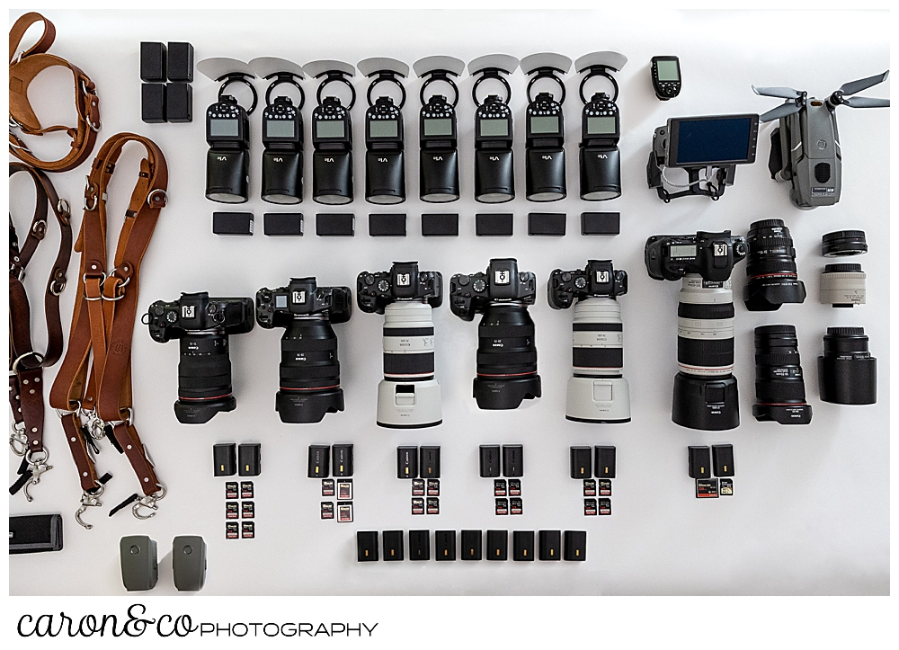 a collection of Maine wedding photography gear, cameras and lenses by Canon, Godox flashes, CF and SD cards, batteries, drone, and camera straps that caron&co photography use as coastal Maine wedding photographers