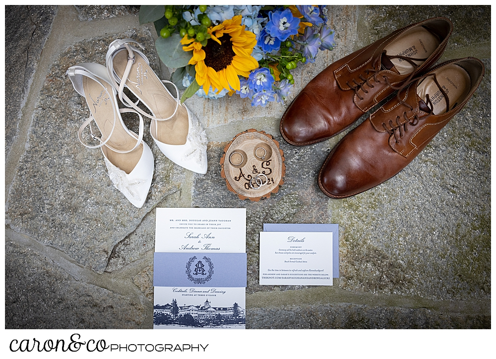 wedding day details: white bridal shoes with straps, mens brown wing tip shoes, a bridal bouquet with blue hydrangea and yellow sun flowers, a blue and white paper suite, and a wooden ring box, all displayed on a slate background